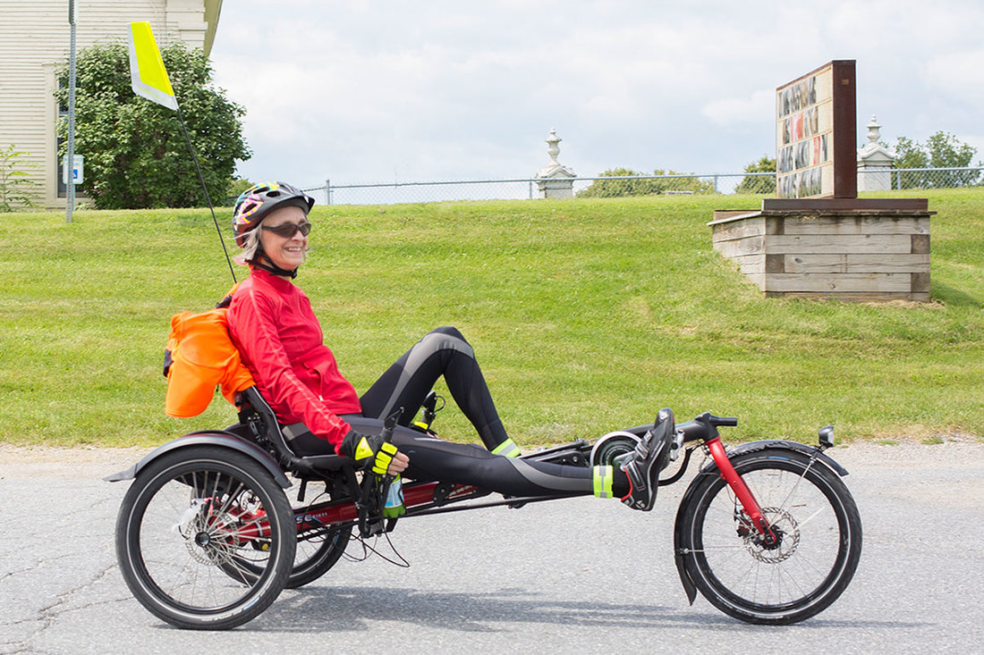 Smiling woman riding a Hase Kettwiesel recumbent trike