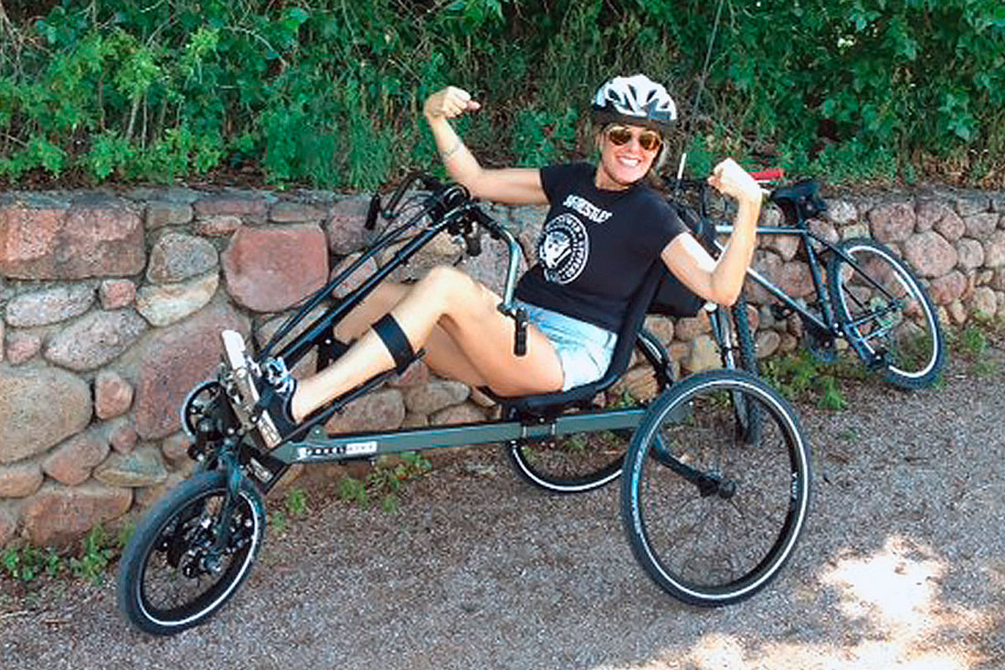 Woman sitting on a BerkelBike combination hand and recumbent trike