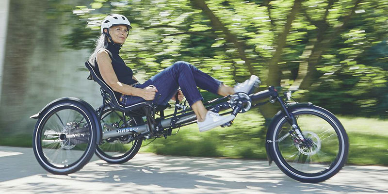 Photo of a woman riding a Hase Bikes Kettwiesel Evo Steps recumbent trike