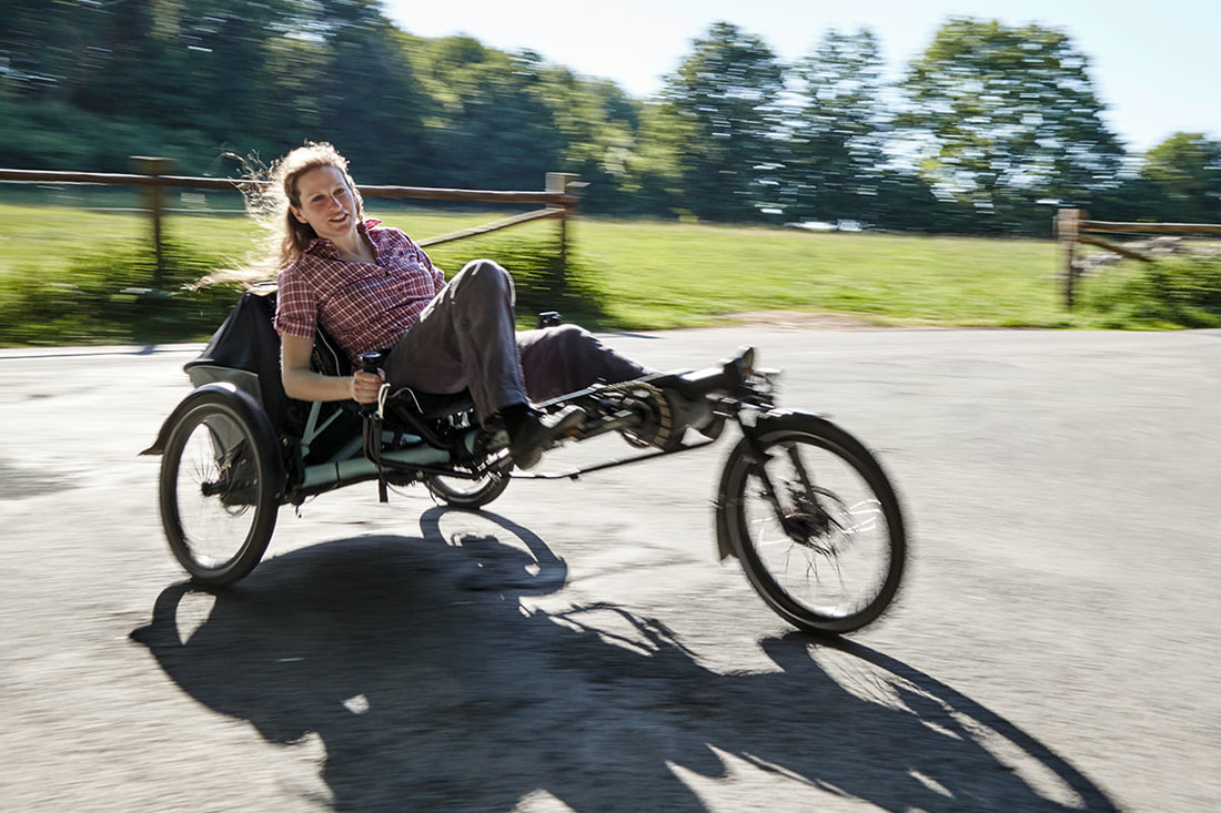 Woman riding a Hase EVOlution recumbent trike with e-motor