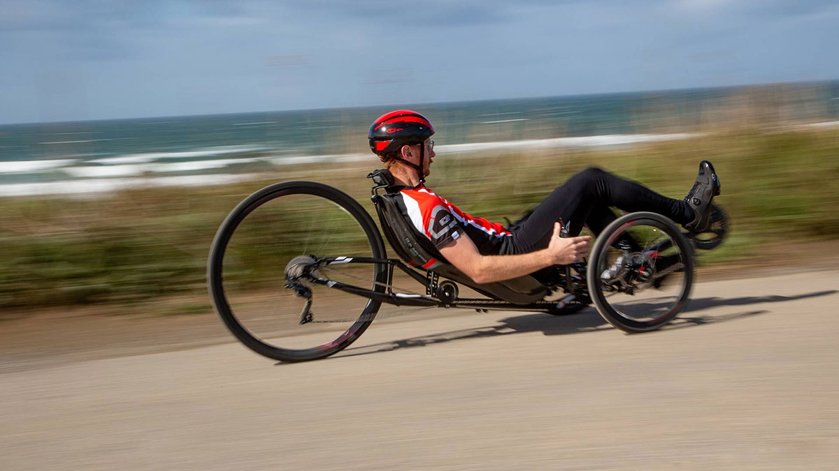 Man riding an ICE VTX recumbent trike on a bike path by the ocean