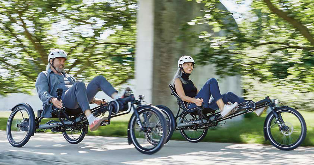Two people riding Hase Kettwiesel EVO STEPS recumbent trikes