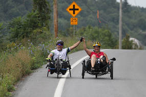 two people riding recumbent trikes on a paved road in summer