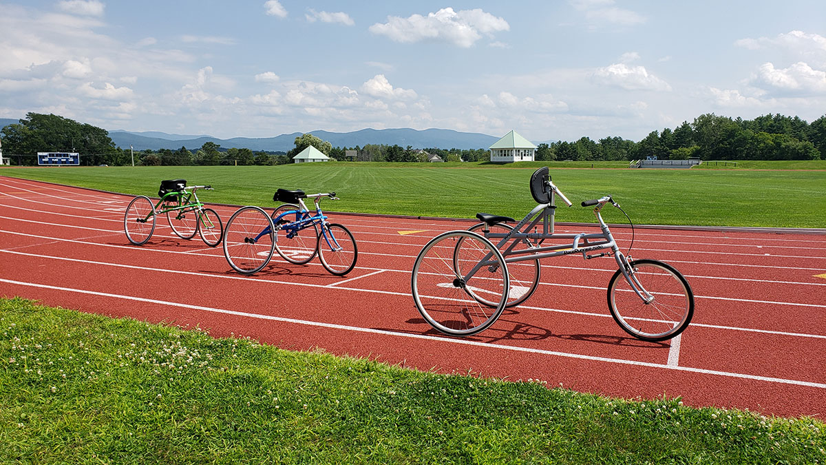 Photo of small, medium and large RAD RaceRunner running trikes on a running track.