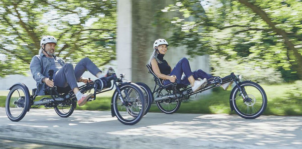 A couple riding Hase Kettwiesel EVO STEPS recumbent e-trikes on a bike path