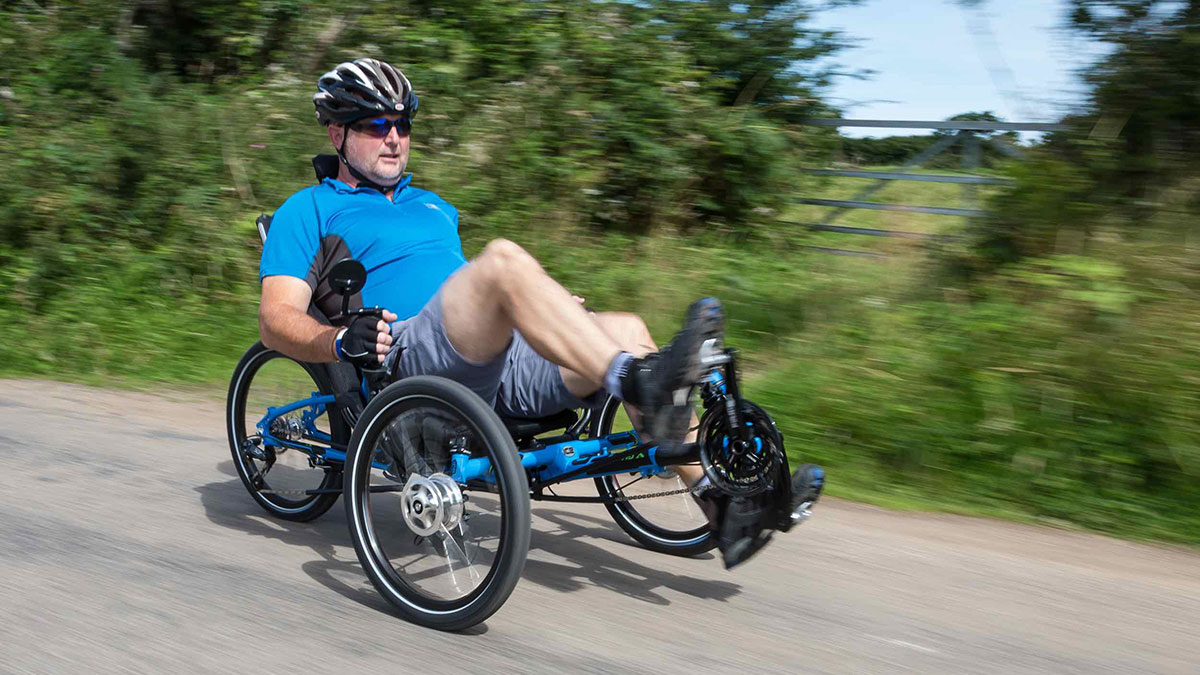 Man riding an ICE recumbent trike on a bike path