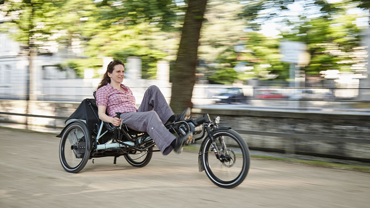 A woman riding a Hase Kettwiesel EVO STEPS recumbent trike in an urban area