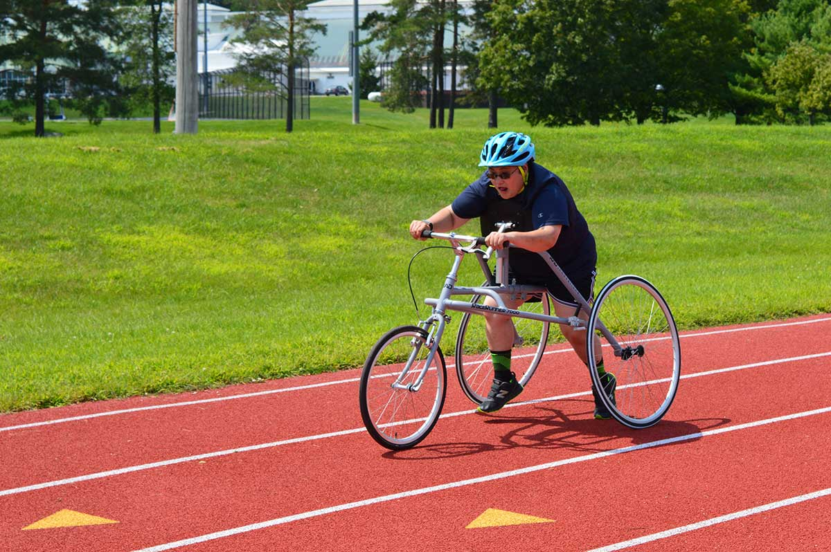 Cari W., a Vermont Special Olympian, tests out a RAD RaceRunner™ running frame at a local track.